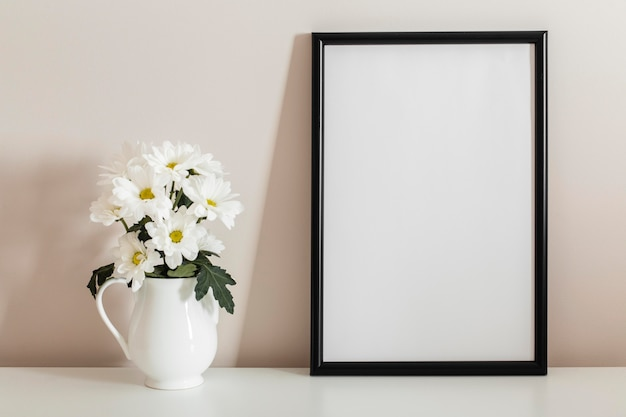 Front view bouquet of white flowers in a vase with empty frame