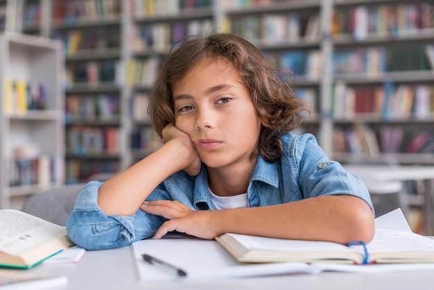 Мальчик вид спереди скучает, пока он делает домашнее задание