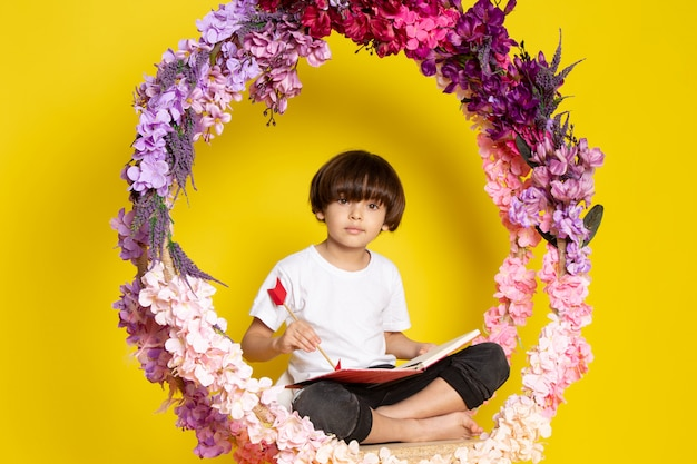 A front view boy cute adorable sweet in white t-shirt siting on the flower made stand on the yellow floor