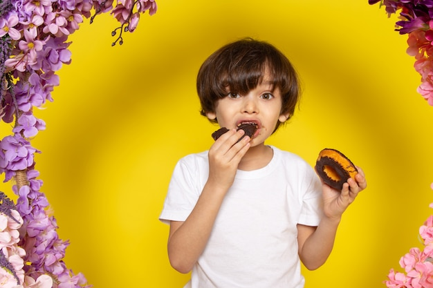 A front view boy eating choco donuts in white t-shirt on the yellow space