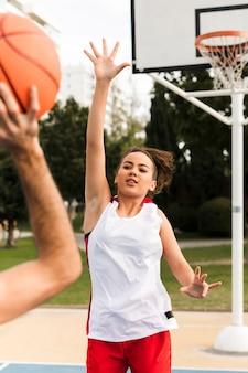 Vista frontale del ragazzo e della ragazza che giocano a basket