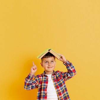 Front view boy holding book on his head