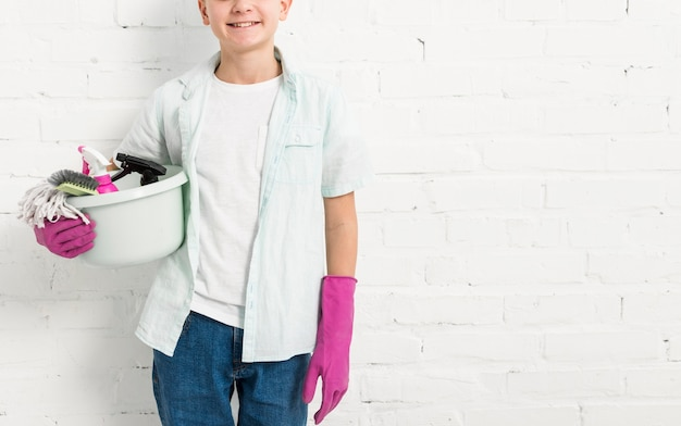 Front view of boy holding cleaning products in bucket