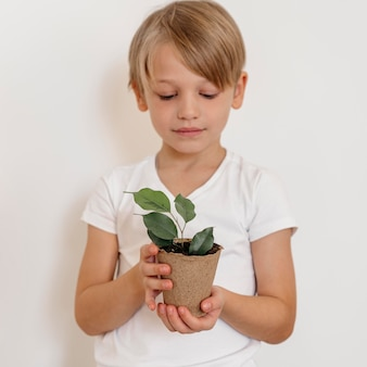 Front view of boy holding pot of plant