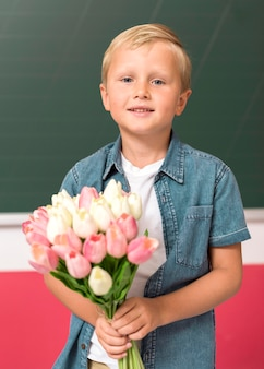 Front view boy holding some flowers for his teacher