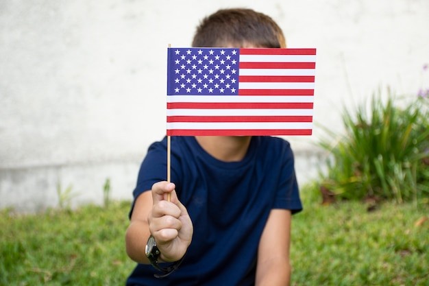 Front view boy holding usa flag over face