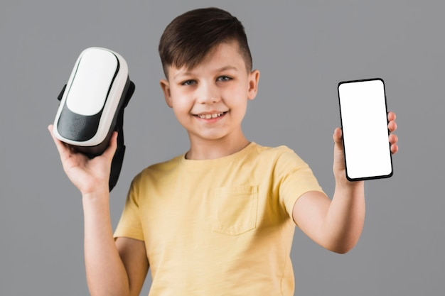 Front view of boy holding virtual reality headset and smartphone