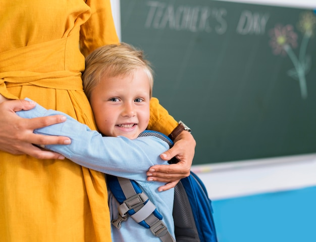 Front view boy hugging his teacher with copy space