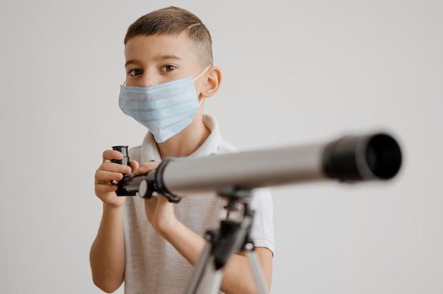 망원경을 사용하는 방법을 배우는 전면보기 소년