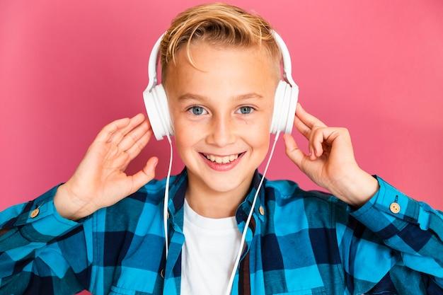 Мальчик вид спереди слушает музыку в наушниках