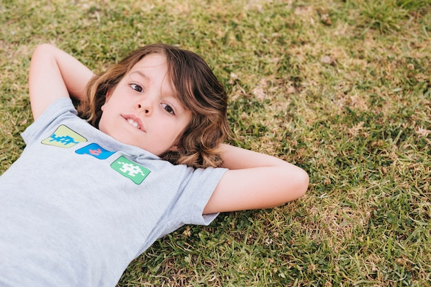 Front view of boy lying on grass