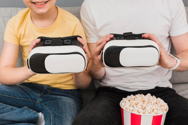 Front view of boy and man holding virtual reality headset with popcorn