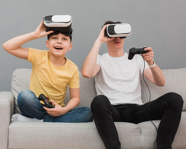 Front view of boy and man playing video games with virtual reality headset