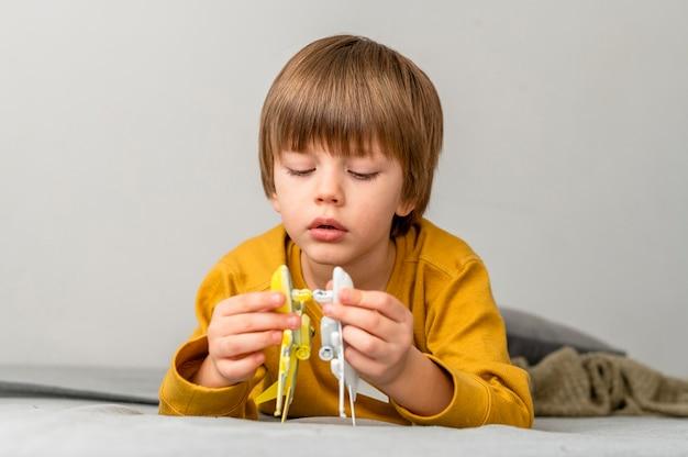 Vista frontale del ragazzo che gioca con le figurine dell'aeroplano
