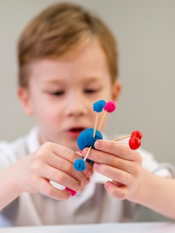 Front view boy playing with colorful atoms game
