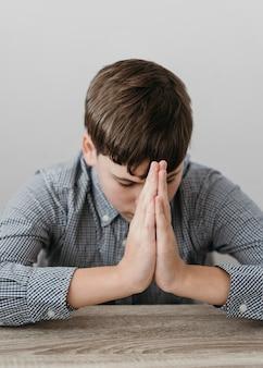 Ragazzo di vista frontale che prega a casa