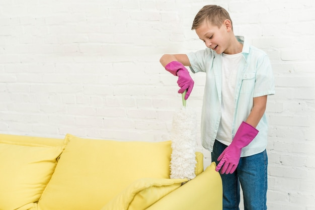 Front view of boy in rubber gloves using duster
