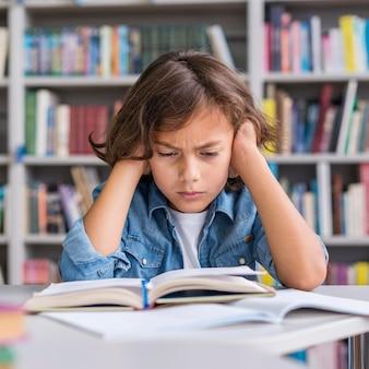 Мальчик вид спереди, усердно думая о том, как решить свою домашнюю работу