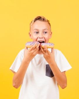 한 번에 두 개의 도넛을 먹으려 고 노력하는 정면 소년