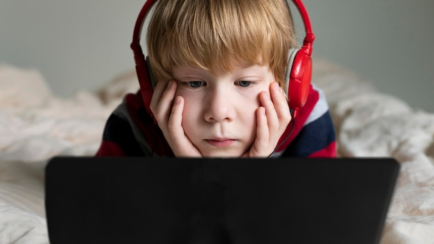 Front view of boy using tablet with headphones