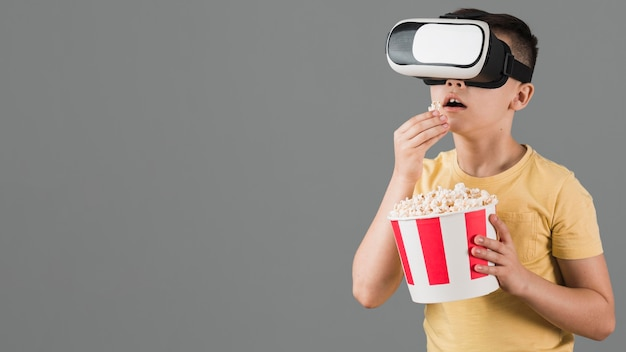 Front view of boy watching movie on virtual reality headset and eating popcorn