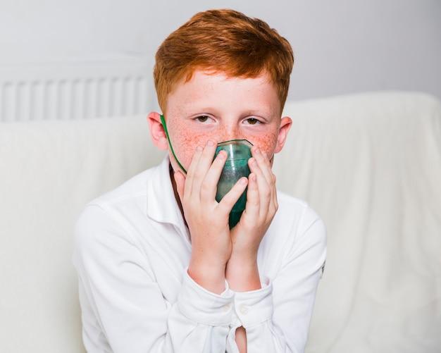 酸素マスクを持つ正面少年
