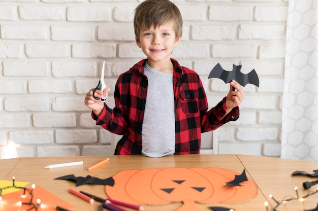 Front view of boy with paper bat