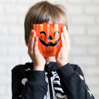 Front view of boy with pumpkin concept