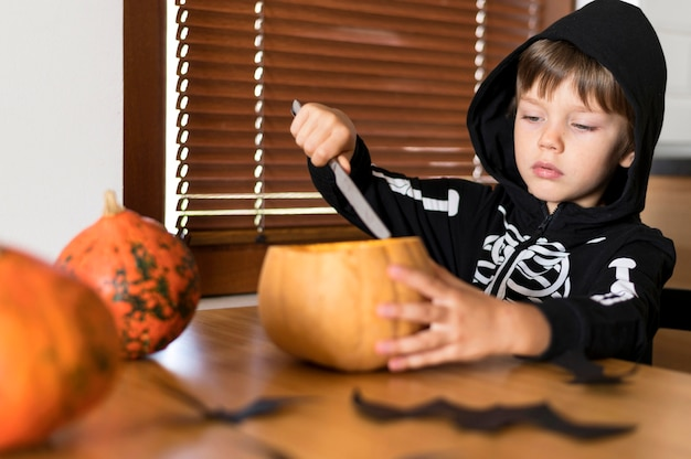 Front view of boy with pumpkin costume concept