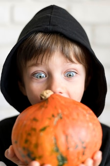 Front view of boy with pumpkin costume concept Premium Photo