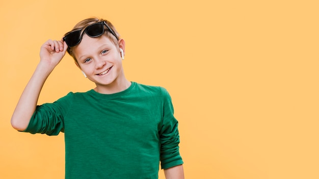 Front view of boy with sunglasses and copy space