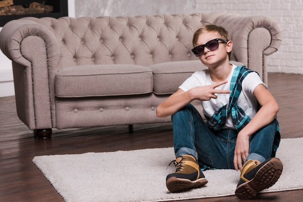 Front view of boy with sunglasses sitting on floor