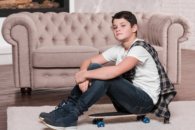 Front view of boy with sunglasses sitting on skateboard