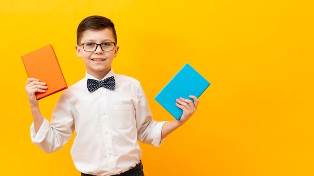 Вид спереди мальчик с двумя книгами