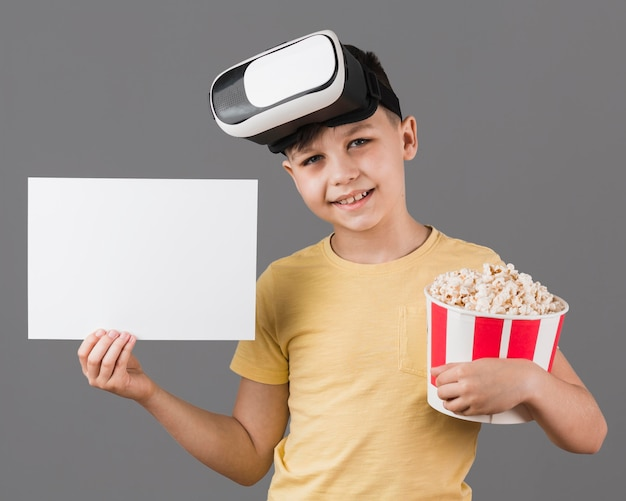 Front view of boy with virtual reality headset holding popcorn and blank paper