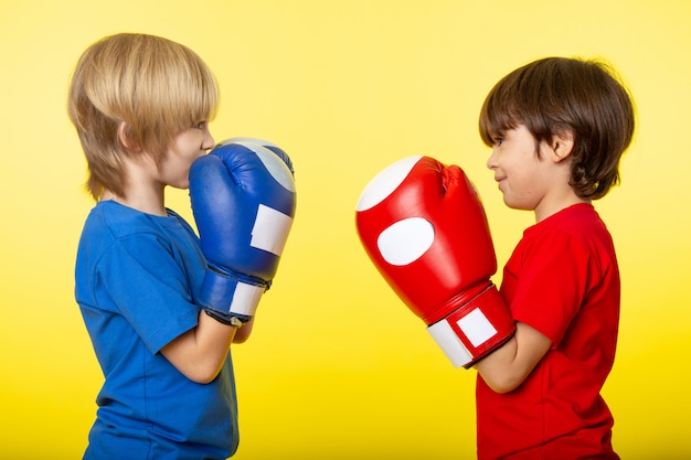 A front view boys faceoff in different colored boxing gloves and t-shirts on the yellow wall