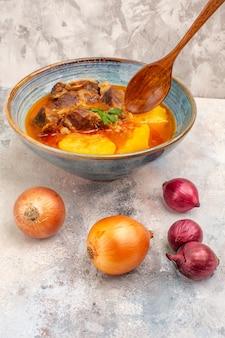 Zuppa di bozbash vista frontale in una ciotola e cipolle su sfondo nudo