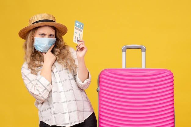 Vista frontale del brainstorming ragazza in viaggio che indossa la maschera che mostra il biglietto e in piedi vicino alla sua borsa rosa su giallo