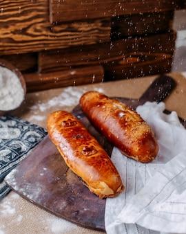Вид спереди хлеба коричневого цвета с мукой, налитой на коричневую поверхность