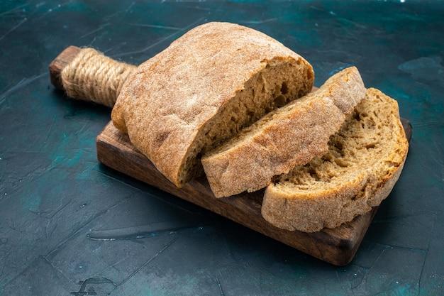 진한 파란색 책상에 구운 빵 덩어리 전면보기.