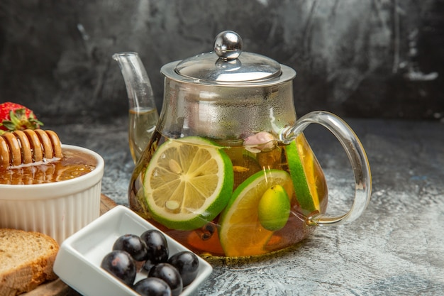 明るい表面の朝食用食品に蜂蜜とお茶を添えた正面図のパン