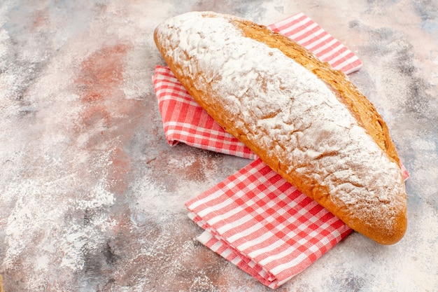 Front view a bread on red kitchen towel on nude background