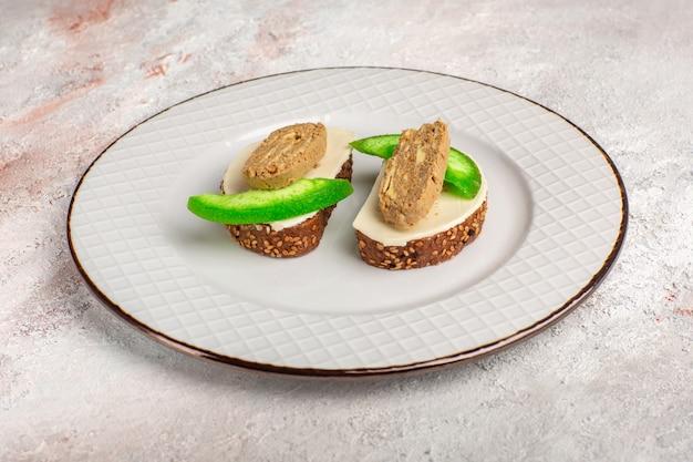 Хлебные тосты, вид спереди с паштетом и ломтиками огурца внутри тарелки на белой поверхности