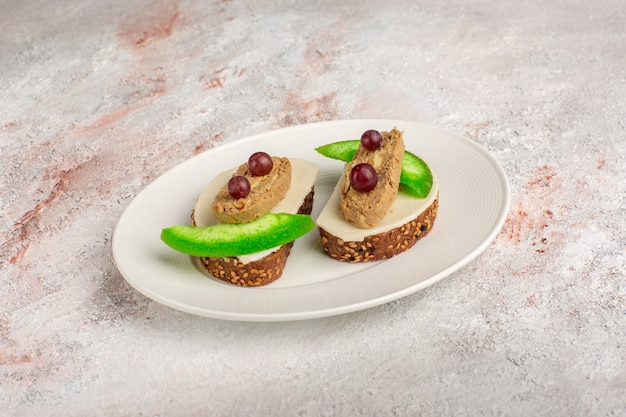 Toast di pane vista frontale con fette di patè e cetriolo all'interno del piatto sulla scrivania bianca