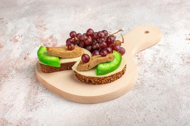 Pane tostato vista frontale con uva patè e fette di cetriolo all'interno della piastra sulla superficie bianca