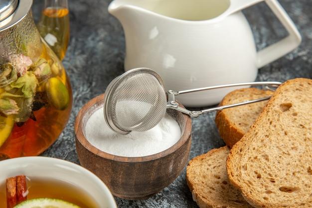 正面図朝食デスクパン蜂蜜と暗い表面のお茶の朝のお茶