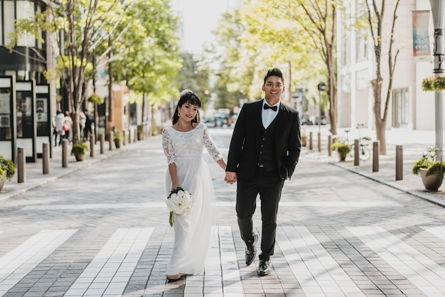 Front view of bride and groom walking on the street