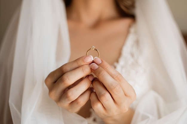 Front view of bride is holding precious engagement ring in hands in front of chest and wedding veil