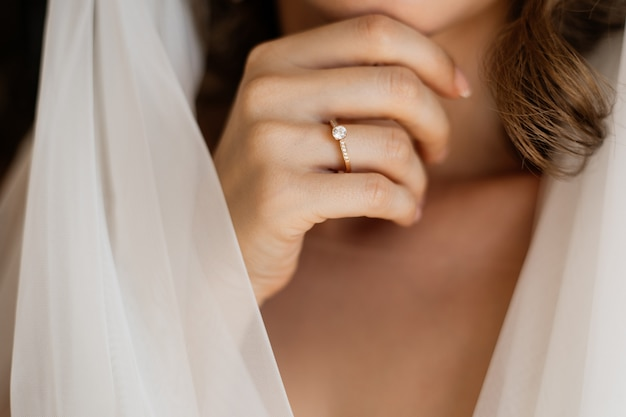 Front view of bride's hand with an engagement ring near the neck and wedding veil