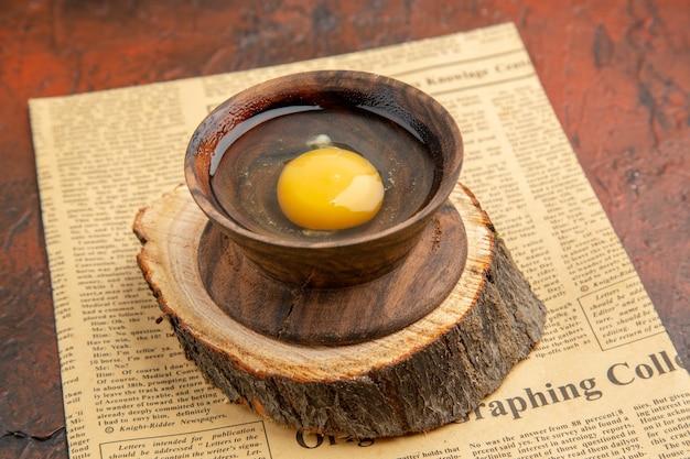 어두운 표면에 접시 안에 날 달걀을 깨진 전면보기